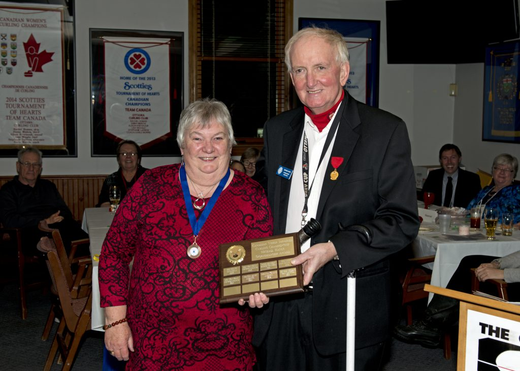 Louise Gillis stands beside Michael Hayes, they are holding the plaque for the Micheal Hayes Sportsmanship Award between them.