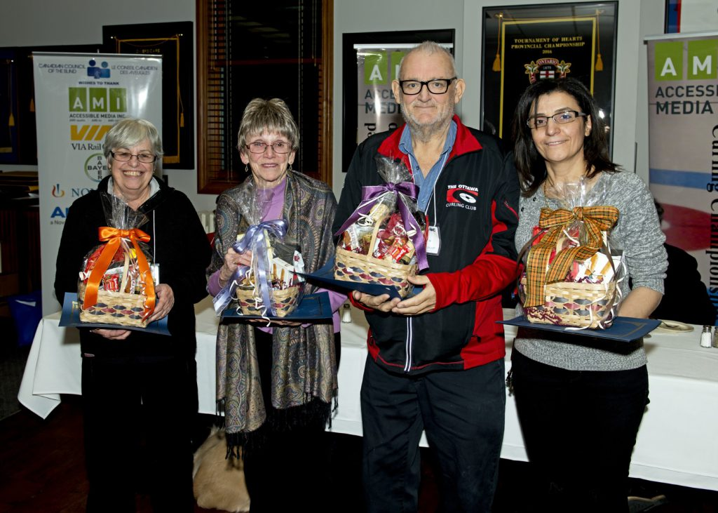 Andree', Barbara, Geoff and Dalal stand in a line holding gift baskets with bows and thank you certificates.