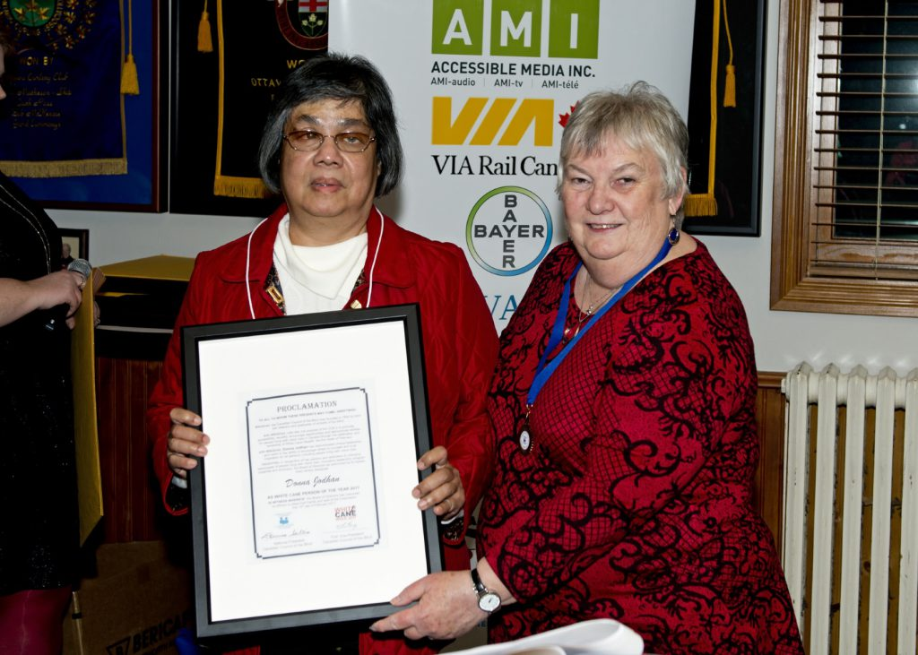Donna stands beside Louise holding her framed certificate. Louise helps steady it with a hand at the bottom.​
