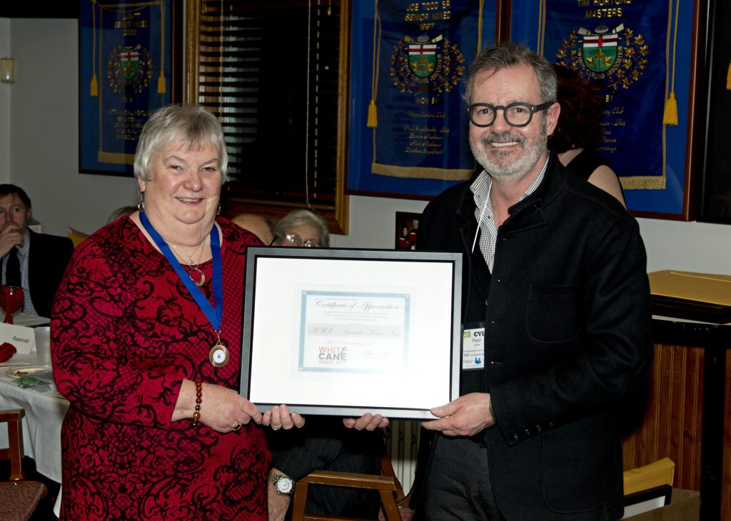 Louise and Peter hold his framed Certificate of Appreciation between them​