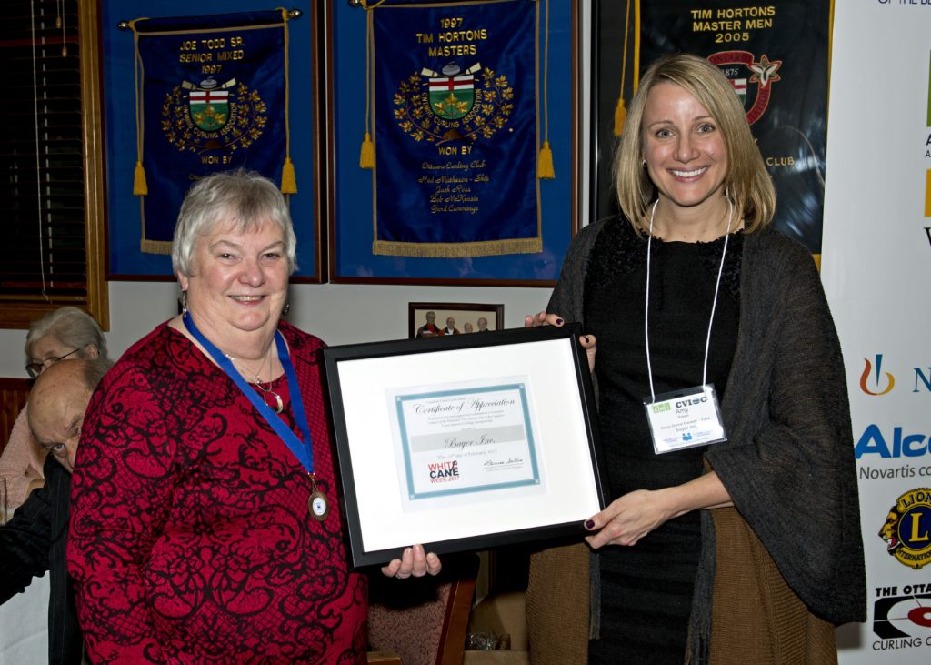 Louise and Amy hold her framed Certificate of Appreciation between them.​