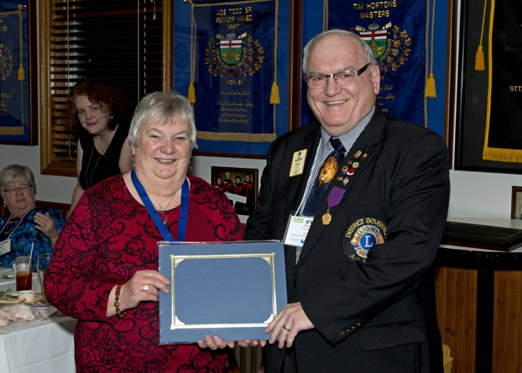 Louise Gillis stands beside Andy Etherington who is wearing his Lions Cub pins and awards on his District Governor Jacket. They are holding a certificate folder between them.