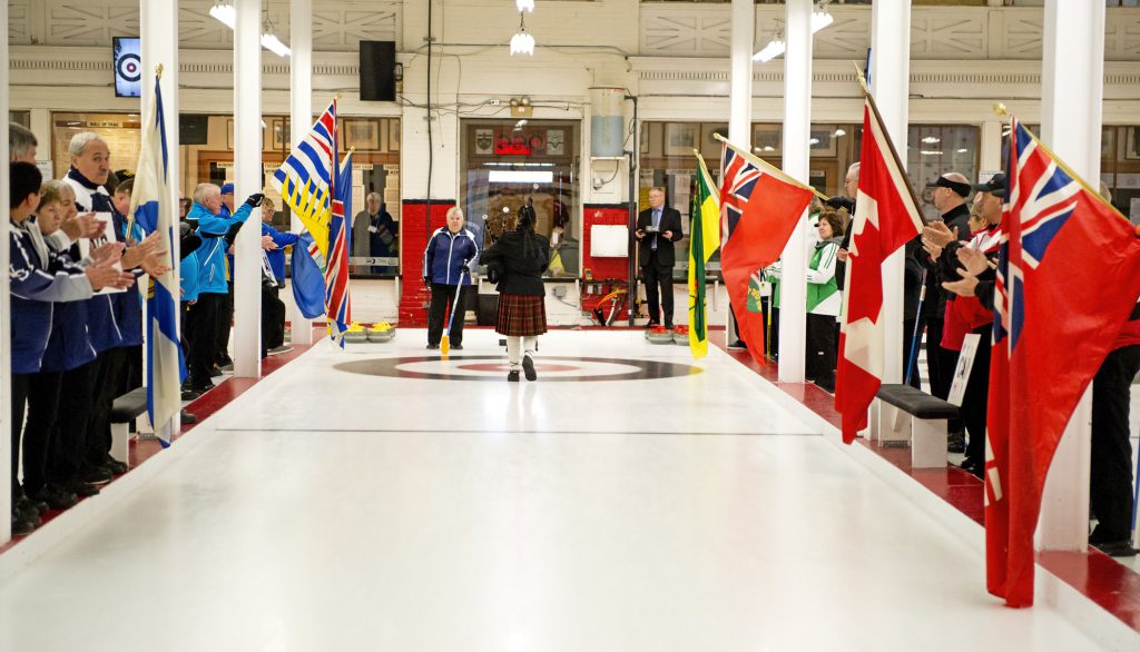 Looking down a curling sheet. A piper wearing a kilt walks away from us. Louise Gillis and Jim Prowse await her at the end of the ice. The curling teams line the sheet wearing their jackets and holding their provincial flags. Teams Nova Scotia, British Columbia, and Alberta are on the left. Teams Manitoba, Canada, Ontario, and Saskatchewan are on the right.​