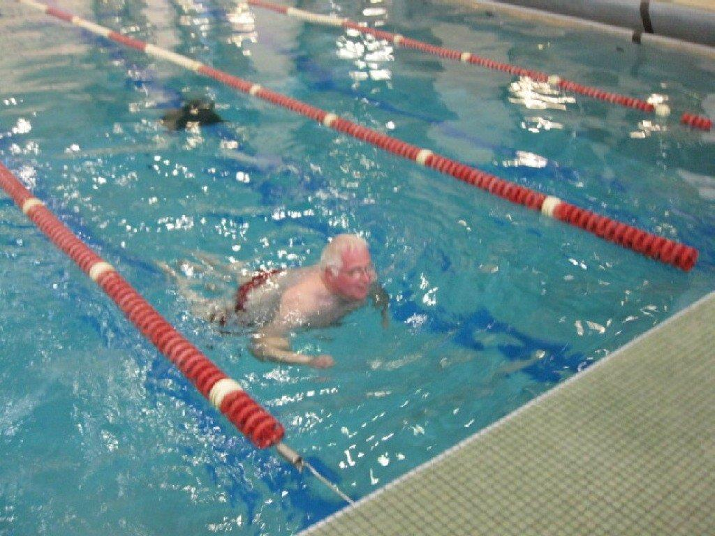 Raymond Young (Sydney, NS Chapter) approaching the finish line with a smile during the swimming competition.