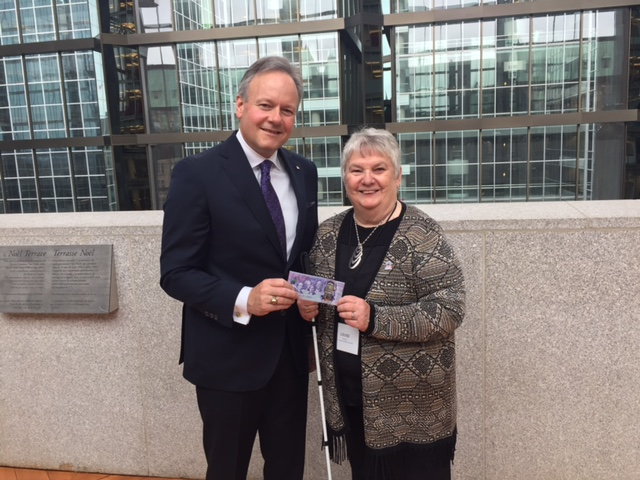 Louise Gillis and Stephen Poloz stand together, holding the new note.