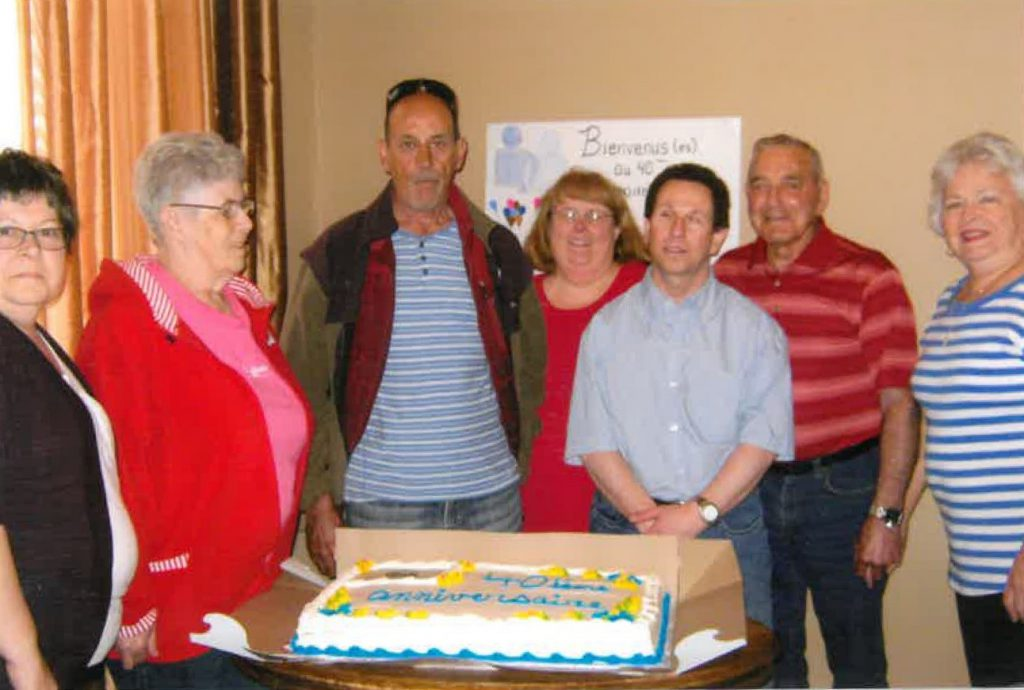 Nancy Roy, Anita Boudreau, François Boudreau, Chantale Doucet, Denis Roy, Thomas Boucher, and Hazel Boucher gather around a square cake decorated in blue and yellow