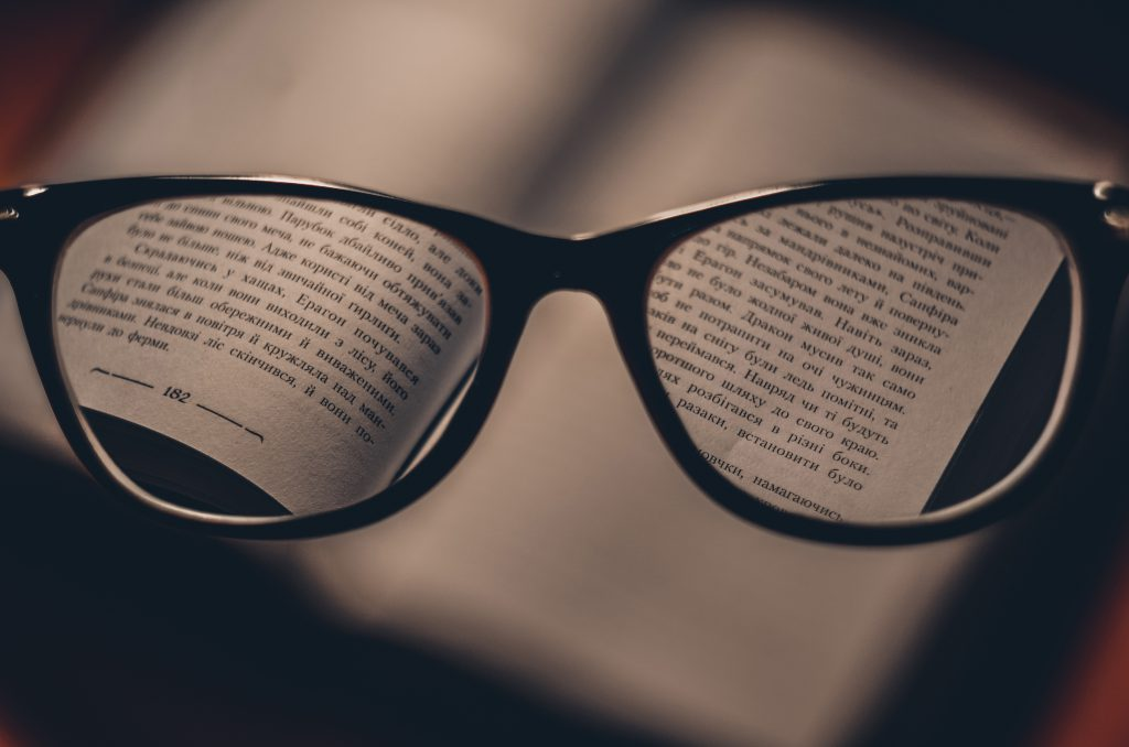 A pair of  black rimmed glasses held in front of a book, bringing the words into focus.