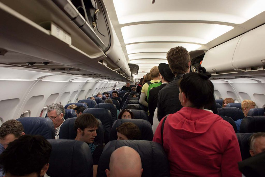 The interior of a plane full of people boarding