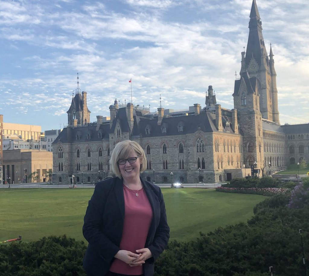 Minister Calra Qualtro stands smiling in front of the parliment buildings.