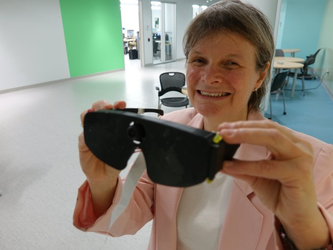 Shelley Ann Morris holds the vision glasses up in front of her.
