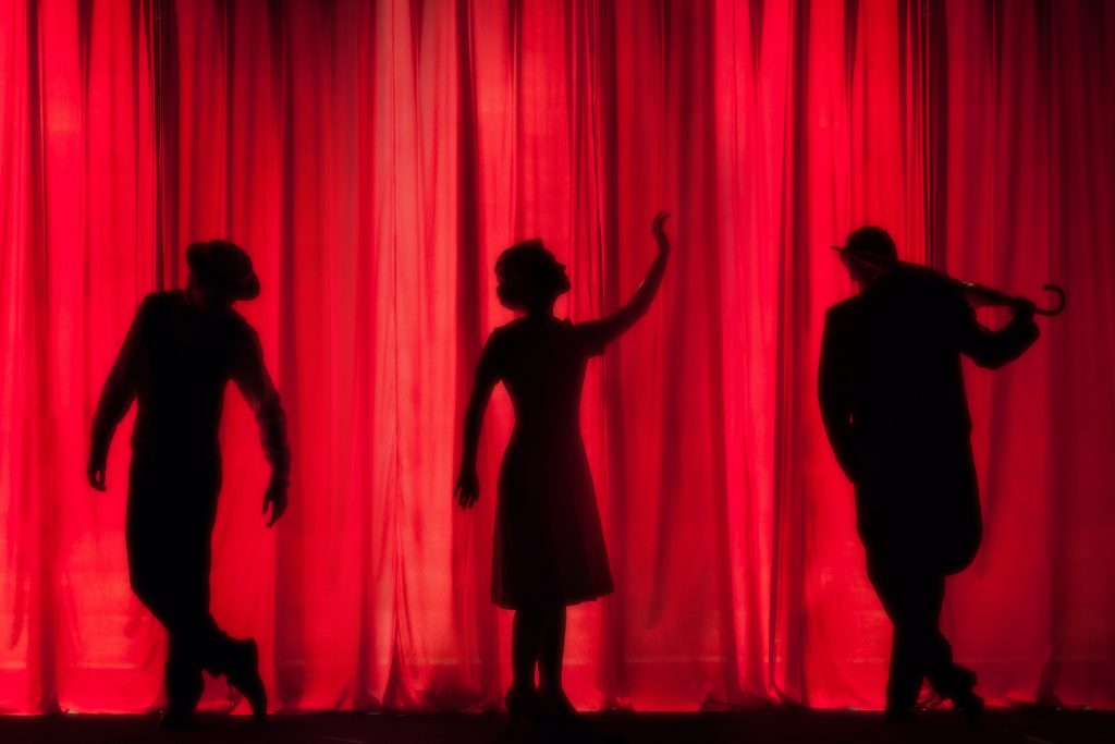 Three silouettes against a red stage curtain.